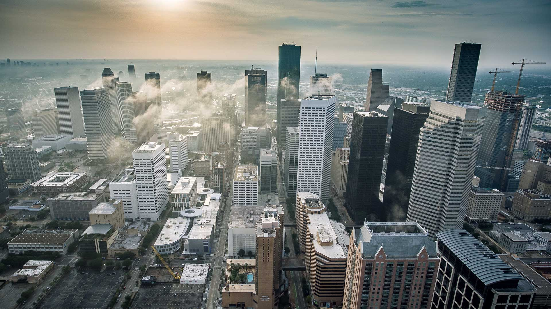 Aerial view of skyscrapers in Houston's downtown core as steam rises from some buildings