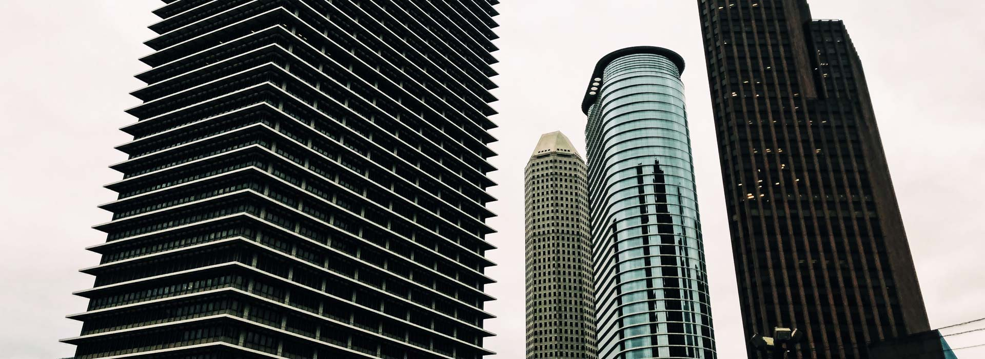 Four tall, commercial high-rise buildings stand next to each other