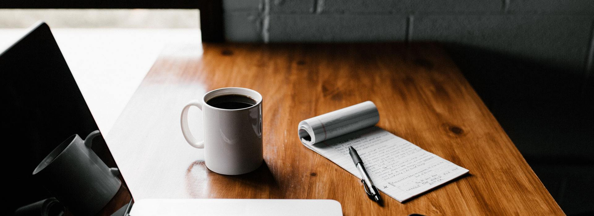 Notepad with writing, a pen, a laptop, and a black coffee in a white mug sit on a wooden desk tabletop